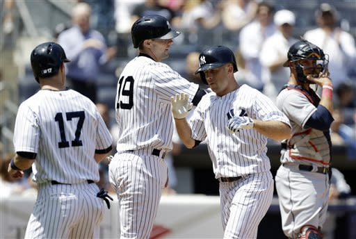 New York Yankees Jayson Nix (17) and Chris Stewart (19) celebrate with Brett Gardner after they scored on Gardner's three-run home run in the third inning of a baseball game against the Cleveland Indians at Yankee Stadium in New York, Wednesday, June 5, 2013. Indians catcher Yan Gomes, right, watches as he adjusts his mask. (AP Photo/Kathy Willens)
