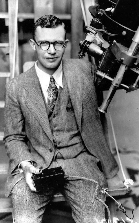 Clyde Tombaugh poses with the telescope through which he discovered the Pluto - Credit: Pluto Stowaway