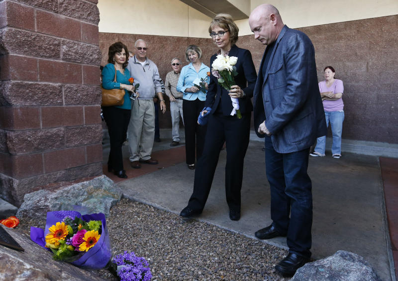 Former Rep. Gabrielle Giffords, front left, holds a bouquet of flowers as she and her husband, Mark Kelly, right, and other shooting victims of the Tucson mass shooting, and family members join her as they returned to the site of a shooting that left her critically wounded to urge key senators to support expanded background checks for gun purchases, Wednesday, March 6, 2013, in Tucson, Ariz. (AP Photo/Ross D. Franklin)