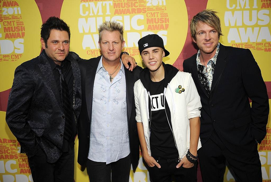 """Bieber Fever is everywhere -- even in Nashville, Tennessee! The 17-year-old pop star -- who sported his newly-pierced ears and a backwards baseball hat -- hit the red carpet at the 10th annual CMT Music Awards with Jay DeMarcus, Gary LeVox, and Joe Don Rooney of Rascal Flatts. JBiebs took home the trophy for Collaborative Video of the Year for """"That Should Be Me,"""" which also featured the country trio. Rick Diamond/<a href=""""http://www.gettyimages.com/"""" target=""""new"""">GettyImages.com</a> - June 8, 2011"""