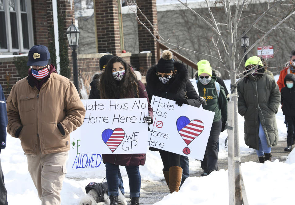 Victoria Wittenberg, 18 second from left, of Grosse Pointe Park and her mom Kelly Wittenberg, center, walk north on Wayburn St. during a walking rally to protest hate and racism in their neighborhood, Sunday, Feb. 21, 2021, in Grosse Pointe Park, Mich., following a white resident's display of a Ku Klux Klan flag in a side window facing their Black neighbor's home. JeDonna Dinges, 57, of Grosse Pointe Park, said the klan flag was hanging next door in a window directly across from her dining room. The incident occurred two weeks ago. (Clarence Tabb, Jr./Detroit News via AP)