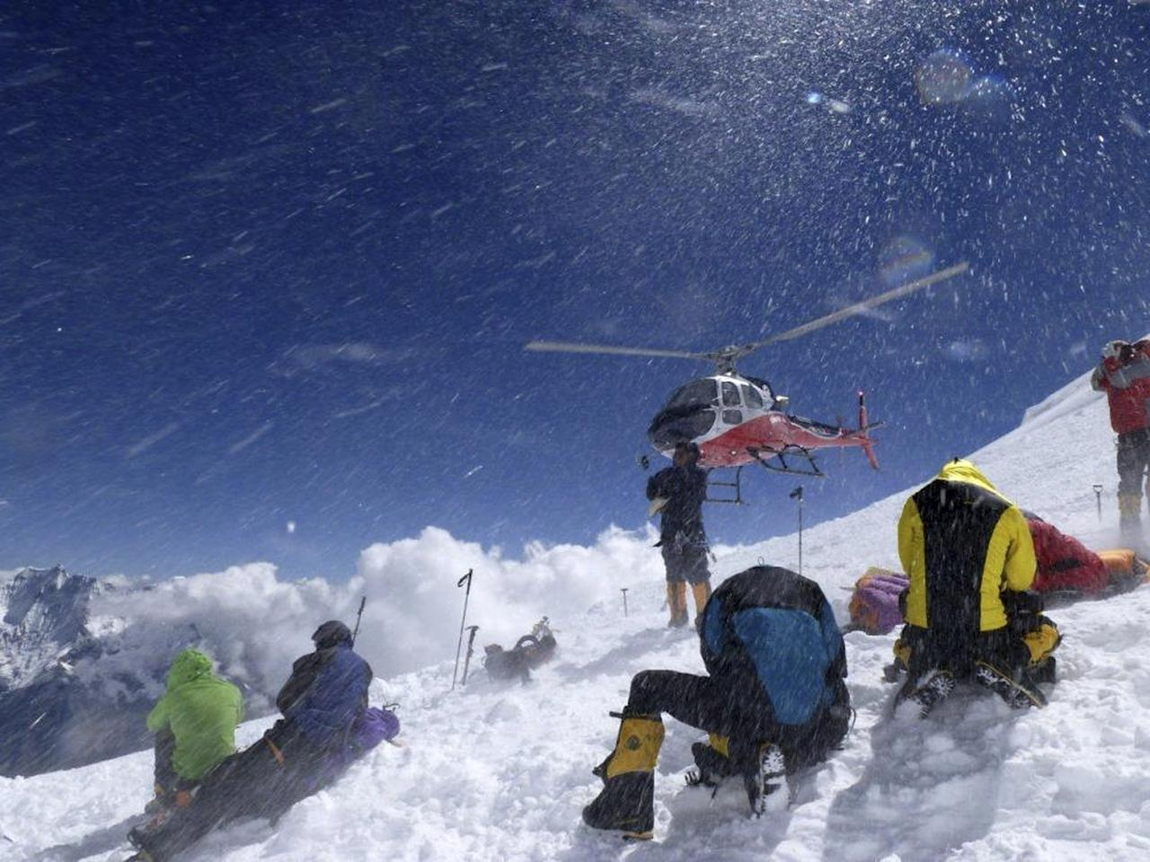 In this picture taken Sunday, Sept. 23, 2012 and released by Alpine Ascents International, a helicopter lifts off carrying survivors from the debris field of an avalanche on Mount Manaslu in northern Nepal. Rescue helicopters flew over the high slopes of the northern Nepal peak again Monday to search for climbers lost in an avalanche that killed at least nine mountaineers and injured others. Many of the climbers were French, German and Italian. (AP Photo/Garrett Madison, Alpine Ascents International)