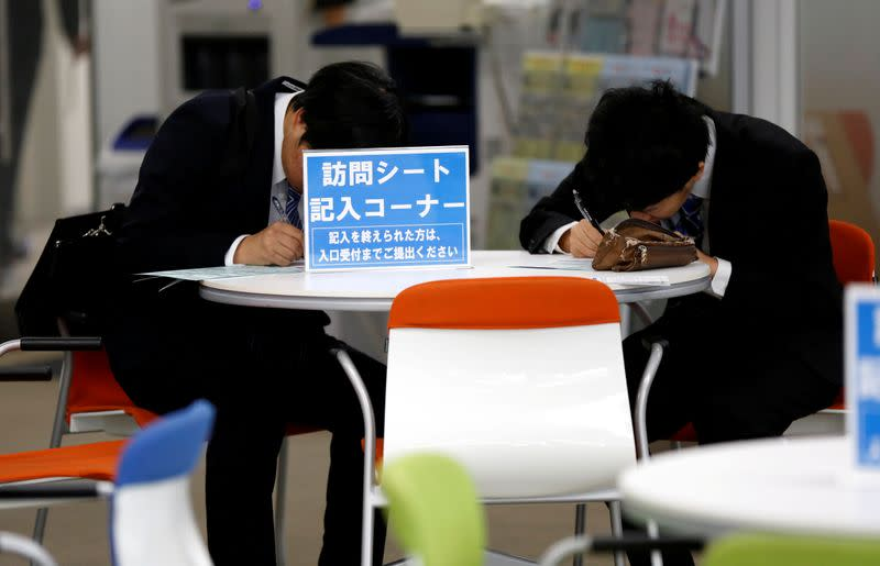 FILE PHOTO: Job seekers attend a job fair held for fresh graduates by ACCESS Humanext Co, in Tokyo