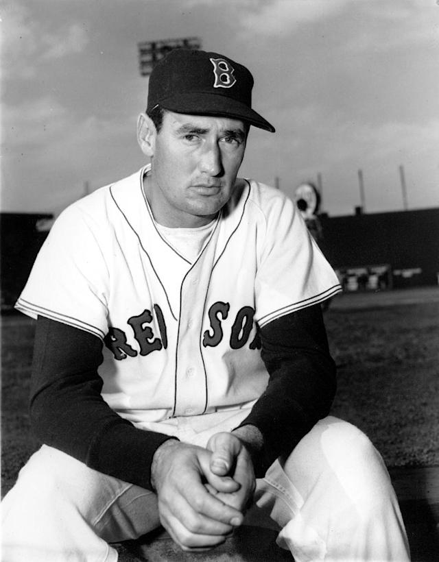 "FILE - In this April 19, 1952 file photo, Boston Red Sox' Ted Williams poses at Fenway Park in Boston. That flowing blue ""Dodgers"" script across the front of the jersey that followed them from Brooklyn. That pointy, ornate ""B"" on the Red Sox cap. Same style, now and then. (AP Photo/File)"