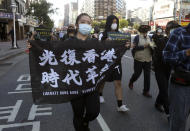 "A protester holds a slogan ""Liberate Hong Kong"" during a march to demand the release of the 12 Hong Kong protesters that have been arrested by mainland Chinese authorities, in Taipei, Taiwan, Sunday, Oct. 25, 2020. A group of 12 people from Hong Kong were allegedly traveling illegally by boat to Taiwan in August when Chinese authorities captured them and detained them. (AP Photo/Chiang Ying-ying)"