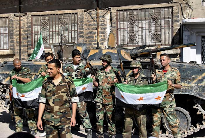 FILE - In this May 12, 2012 file photo, Syrian army soldiers hold the Syrian revolution flags as they stand in front their armored personnel carrier shortly after they defected and joined the rebels at Khaldiyeh neighborhood, in Homs province, central Syria. A top Syrian cleric's appeal for men to join the army raises the question of whether President Bashar Assad is running out of soldiers and prompts a pro-government newspaper to declare the military can battle insurgents for years to come. The civil war has eroded one of the Arab world's biggest armies, and pro-Assad militiamen are increasingly filling in for troops. (AP Photo/Fadi Zaidan, File)