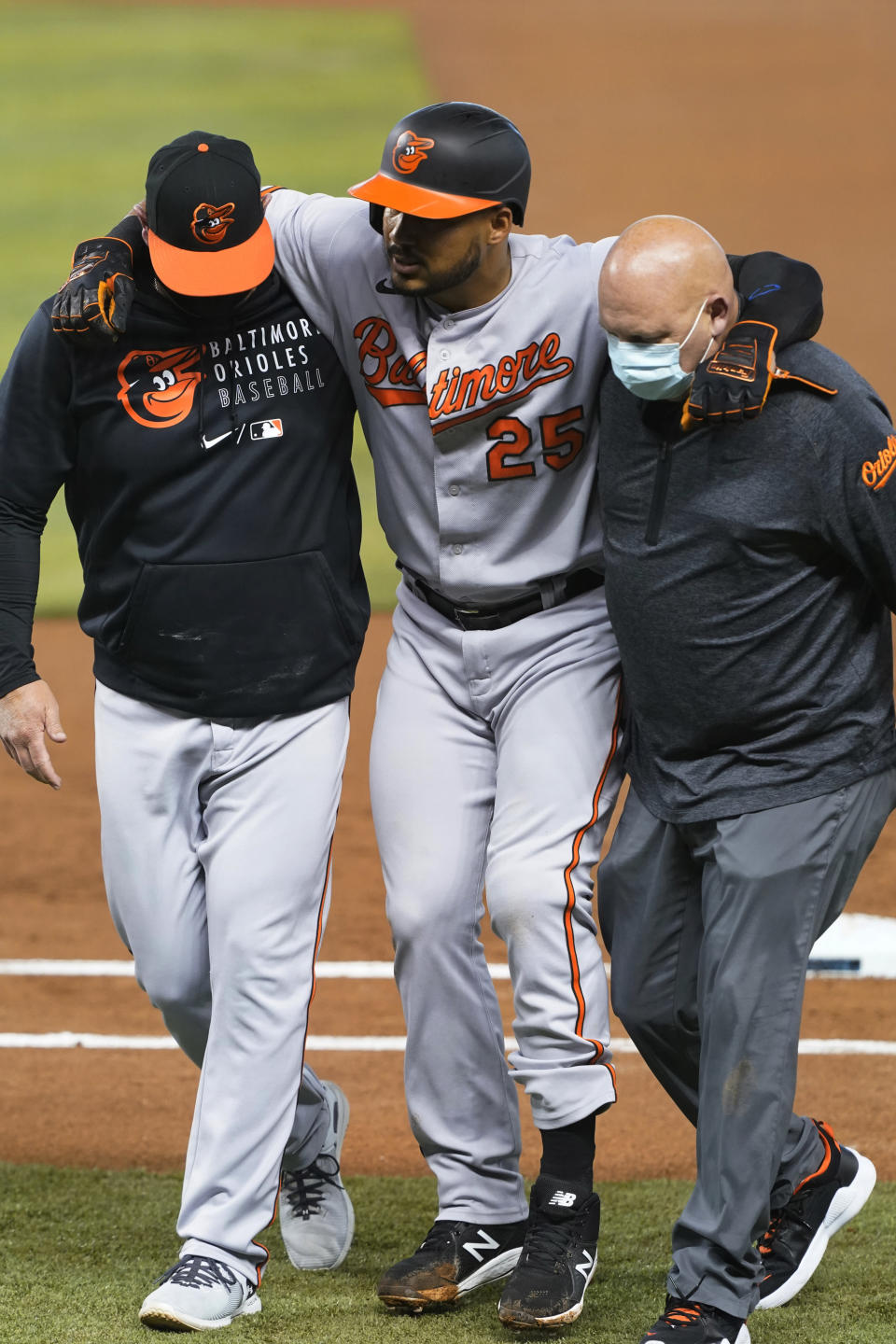 Baltimore Orioles' Anthony Santander (25) is assisted off the field after he was injured during the first inning of a baseball game against the Miami Marlins, Tuesday, April 20, 2021, in Miami. (AP Photo/Marta Lavandier)