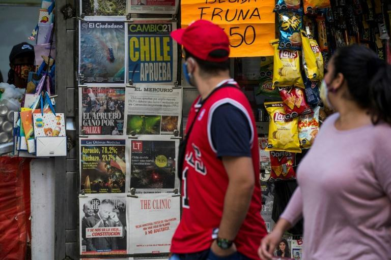 People look at the covers of Chilean newspapers as they walk past a kiosk the day after a referendum in Santiago on October 26, 2020