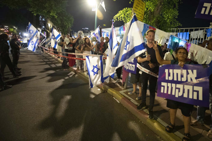 """Israeli left-wing protesters chant slogans and hold flags during a demonstration for the forming of a new government in the central Israeli city of Ramat Gan, Wednesday, June 2, 2021. Hebrew sign reads: """"We are the hope"""". (AP Photo/Sebastian Scheiner)"""