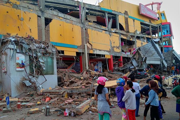 <p>Residents stand in front of a damaged shopping mall after an earthquake hit Palu, Sulawesi Island, Indonesia on Sept. 29, 2018. (Photo: Antara Foto/Rolex Malaha via Reuters) </p>