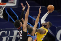 Los Angeles Lakers forward LeBron James, right, shoots as Oklahoma City Thunder forward Isaiah Roby (22) and forward Darius Bazley defend during the first half of an NBA basketball game Wednesday, Jan. 13, 2021, in Oklahoma City. (AP Photo/Sue Ogrocki)