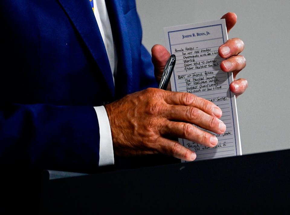 Democratic nominee Joe Biden brings notes about Kamala Harris to a press conference in Delaware: AFP via Getty Images