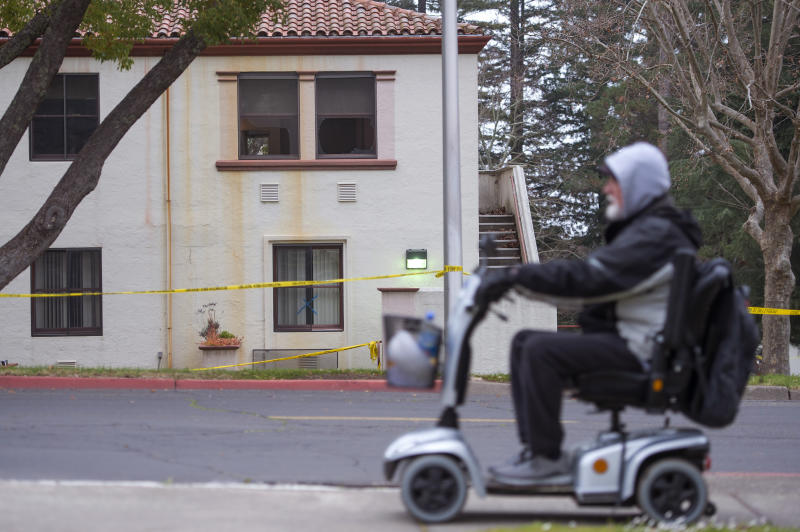 A man passes by damaged windows, the morning after a hostage situation at the Veterans Home of California in Yountville, Calif., on Saturday, March 10, 2018. A daylong siege at The Pathway Home ended Friday evening with the discovery of four bodies, including the gunman, identified as Albert Wong, a former Army rifleman who served a year in Afghanistan in 2011-2012. (AP Photo/Josh Edelson)