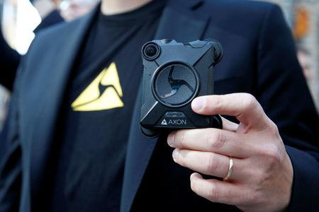 Josh Isner, Executive Vice President of Global Sales and Representatives of Axon (formerly known Taser International Inc.) holds one of his company's body cameras while visiting the Nasdaq MarketSite in New York City, U.S. April 5, 2017. REUTERS/Brendan McDermid