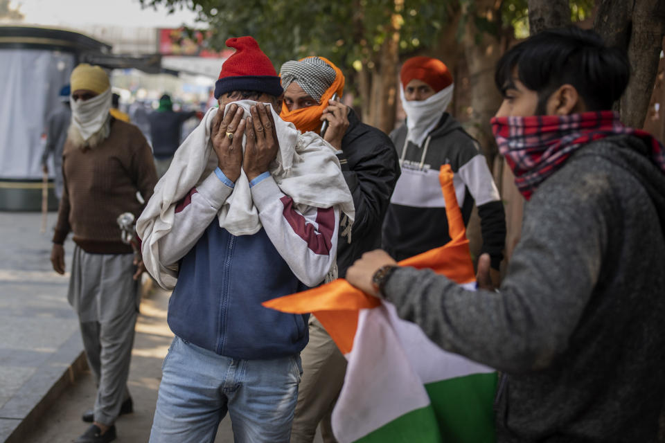 Protesting farmers cover their faces to escape tear gas smoke as they march to the capital breaking police barricades during India's Republic Day celebrations in New Delhi, India, Tuesday, Jan. 26, 2021. Tens of thousands of farmers drove a convoy of tractors into the Indian capital as the nation celebrated Republic Day on Tuesday in the backdrop of agricultural protests that have grown into a rebellion and rattled the government. (AP Photo/Altaf Qadri)