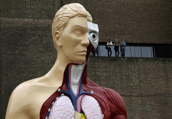 "Visitors stand at a balcony behind the Damien Hirst sculpture ""Hymn"" outside the Tate Modern gallery in London August 21, 2012."