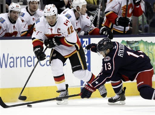 Calgary Flames' Jarome Iginla, left, works for the puck against Columbus Blue Jackets' Cam Atkinson in the first period of an NHL hockey game in Columbus, Ohio, Friday, March 22, 2013. (AP Photo/Paul Vernon)