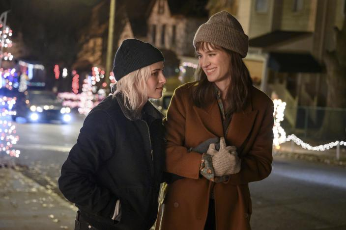 """This image released by Hulu shows Kristen Stewart, left, and Mackenzie Davis in a scene from """"Happiest Season."""" The film took home the GLAAD award for Outstanding Film - Wide Release. (Jojo Whilden/Hulu via AP)"""