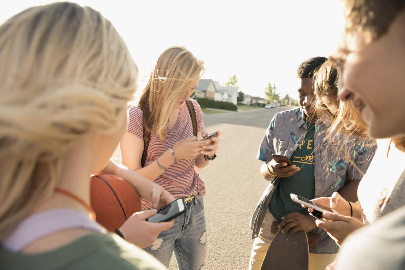 Teenage friends hanging out, texting with cell phone on sunny street