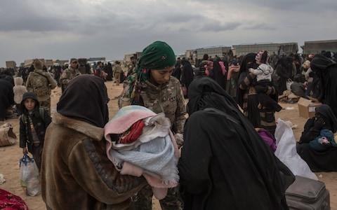 Women wait to board lorries taking them out of the last patch of Islamic State territory in Baghouz - Credit: Sam Tarling, The Telegraph