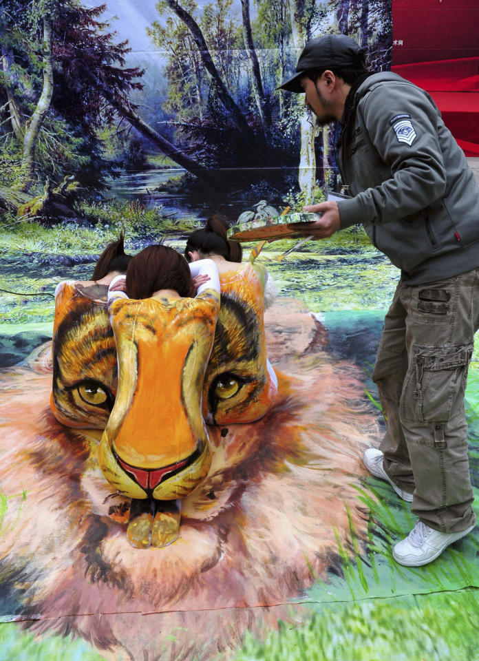 An artist paints a 3D body painting depicting a tiger's face on the backs of three models in Fuzhou, Fujian province January 3, 2012. The models were wearing white shirts for the painting as a call for increased awareness of protecting endangered animals. REUTERS/China Daily