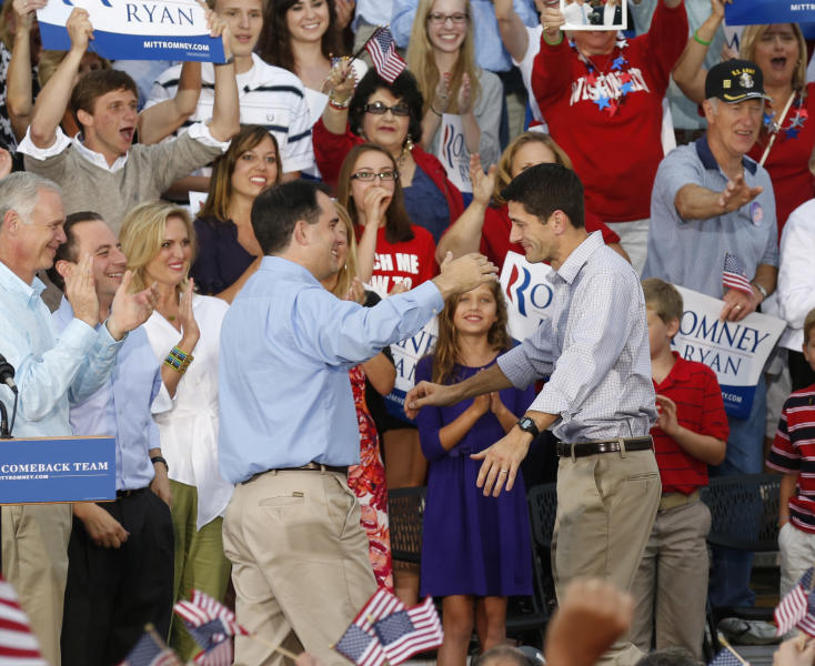 Vice presidential running mate Rep. Paul Ryan, R-Wis, right, greets Wisconsin Gov. Scott Walker at his welcome home rally Sunday, Aug., 12, 2012 in Waukesha, Wis. (AP Photo/Jeffrey Phelps)