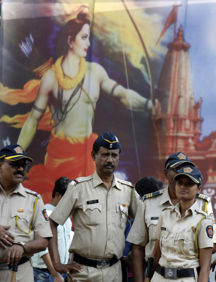 Police officers stand guard in front of a poster of Hindu god Rama outside the Bhartiya Janata Party (BJP) head office in Mumbai, Saturday, Nov. 9, 2019. India's Supreme Court on Saturday ruled in favor of a Hindu temple on a disputed religious ground and ordered that alternative land be given to Muslims to build a mosque. The dispute over land ownership has been one of the country's most contentious issues. (AP Photo/Rajanish Kakade)