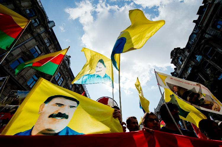 Demonstrators hold up flags with the portrait of Kurdish leader Abdullah Öcalan as they take part in a rally on August 9, 2014 in Frankfurt am Main, Germany