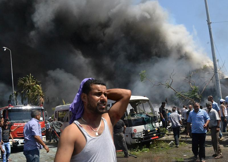 A Lebanese man reacts at the scene of an explosion in the northern city of Tripoli, Lebanon, Friday Aug. 23, 2013. Lebanon's official news agency says dozens of people have been killed by twin explosions outside two Sunni mosques in a northern city. The explosions in Tripoli come amid rising tensions in Lebanon resulting from Syria's civil war, which has sharply polarized the country along sectarian lines and between supporters and opponents of the regime of President Bashar Assad. Tripoli has previously seen clashes between Sunnis and Alawites, a Shiite offshoot sect to which Assad belongs.(AP Photo)