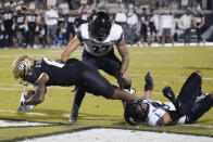 Central Florida wide receiver Marlon Williams, left, scores a touchdown as he gets past Cincinnati linebacker Darrian Beavers, center, and safety Darrick Forrest, right, during the second half of an NCAA college football game, Saturday, Nov. 21, 2020, in Orlando, Fla. (AP Photo/John Raoux)
