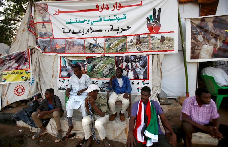 Sudanese men displaced from Darfur sit next to a tent outside the military headquarters in the capital Khartoum at the ongoing sit-in (AFP Photo/ASHRAF SHAZLY)