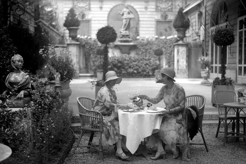 """Ladies drinking tea in the garden of the <a href=""""https://www.cntraveler.com/hotels/france/paris/hotel-ritz-paris?mbid=synd_yahoo_rss"""" rel=""""nofollow noopener"""" target=""""_blank"""" data-ylk=""""slk:Ritz Paris"""" class=""""link rapid-noclick-resp"""">Ritz Paris</a>, one of the most <a href=""""https://www.cntraveler.com/galleries/2015-09-11/from-raffles-to-the-ritz-10-of-the-worlds-most-iconic-hotels-pellicano?mbid=synd_yahoo_rss"""" rel=""""nofollow noopener"""" target=""""_blank"""" data-ylk=""""slk:iconic hotels"""" class=""""link rapid-noclick-resp"""">iconic hotels</a> in the city—and the entire world."""