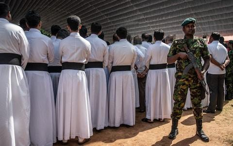 A soldier guards clergymen attending the mass funeral - Credit: Carl Court/ Getty Images AsiaPac