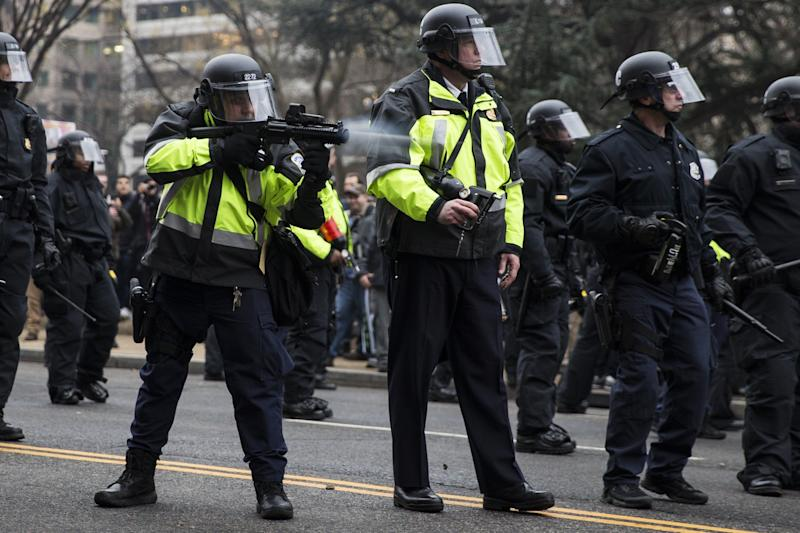 A police officer fires a beanbag round at anti-Trump protesters, Jan. 20, 2017.