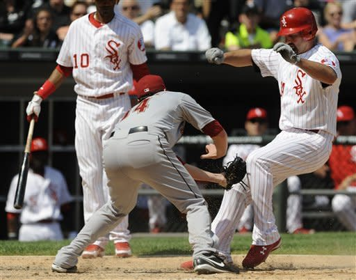Houston Astros starting pitcher Lucas Harrell left, tags out Chicago White Sox's Paul Konerko at home plate in the sixth inning during a baseball game in Chicago, Sunday, June 10, 2012. (AP Photo/Paul Beaty)