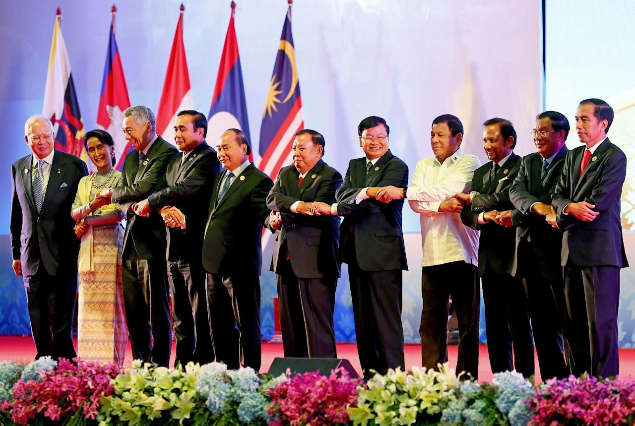 In this Tuesday, Sept. 6, 2016, file photo, Southeast Asian leaders link arms at the opening of the 28th and 29th ASEAN Summits and other related summits in the National Convention Center in Vientiane, Laos. Leaders are, from left; Malaysia's Prime Minister Najib Razak, Myanmar's State Counsellor and Foreign Minister Aung San Suu Kyi, Singapore's Prime Minister Lee Hsien Loong, Thailand's Prime Minister Prayuth Chan-ocha, Vietnam's President Tran Dai Quang, Laos' President Bounnhang Vorachith, Laos' Prime Minister Thongloun Sisoulith, Philippine President Rodrigo Duterte, Brunei's Sultan Hassanal Bolkiah, Cambodia's Prime Minister Hun Sen and Indonesia's President Joko Widodo. (AP Photo/Bullit Marquez, File)