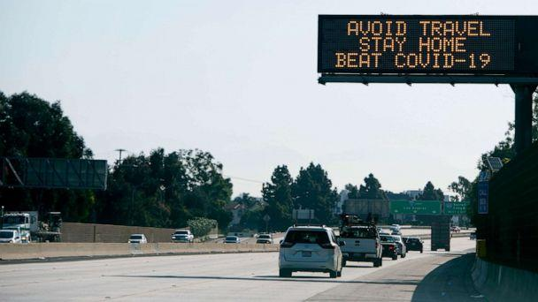 PHOTO: A sign asking for drivers to 'avoid travel and stay home' due to the spread of the COVID-19, the disease caused by the novel coronavirus, is displayed over the I-10 freeway in Santa Monica, California, on April 14, 2020. (Valerie Macon/AFP via Getty Images)