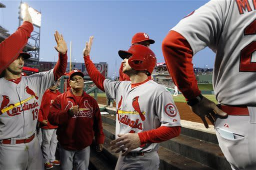 St. Louis Cardinals right fielder Shane Robinson, center, celebrates scoring with this teammates during the fourth inning of a baseball game against the Washington Nationals at Nationals Park on Tuesday, April 23, 2013, in Washington. (AP Photo/Alex Brandon)