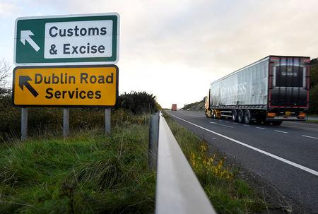 FILE PHOTO: A Guinness truck passes a sign for Customs and Excise on a road near the border with Ireland near Kileen, Northern Ireland