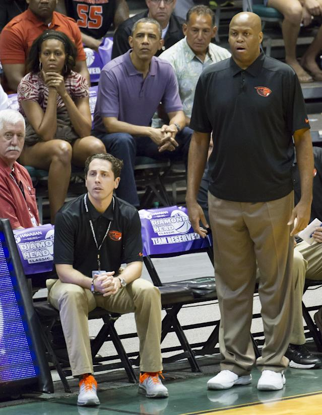 FILE - In this Dec. 22, 2013 file photo, Oregon State head coach Craig Robinson, right, watches his team play Akron along with his brother-in-law President Barack Obama, top center, and his sister the first lady Michelle Obama, top left, in the first half of an NCAA college basketball game at the Diamond Head Classic, in Honolulu. Oregon State fired Robinson, Monday, May 5, 2014, after six seasons without making the NCAA tournament. (AP Photo/Eugene Tanner, File)