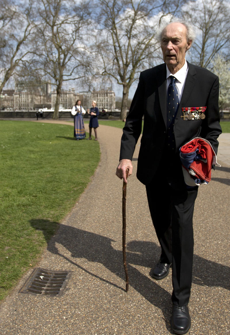 FILE - In this Thursday, April 25, 2013 file photo, Norwegian war hero and resistance fighter Joachim Roenneberg holds a Union flag as he walks in a park near the Palace of Westminster, after receiving the Union Jack Medal for his efforts and cooperation with the British during the second World War. Norway's leader says World War II saboteur Roenneberg has died at 99, it was reported on Monday, Oct. 22, 2018. In 1943, Roenneberg headed the four-man team that blew up a plant producing heavy water, which Nazi Germany could have used to produce nuclear weapons. P (AP Photo/Alastair Grant, File)