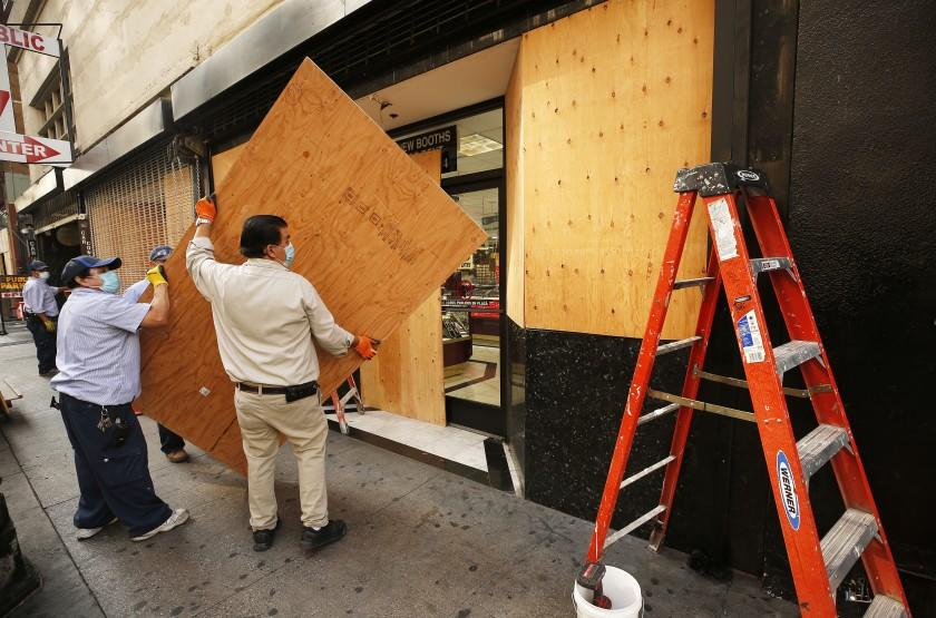 LOS ANGELES, CA - NOVEMBER 02: Workmen build a plywood wall at the storefront of a complex of jewelry stores located at South Broadway and 6th Street in downtown Los Angeles in preparation for possible civil unrest in downtown L.A. as a number of retail store fronts are boarding up in advance of an anxious election day across L.A. on Tuesday. Downtown on Monday, Nov. 2, 2020 in Los Angeles, CA. (Al Seib / Los Angeles Times