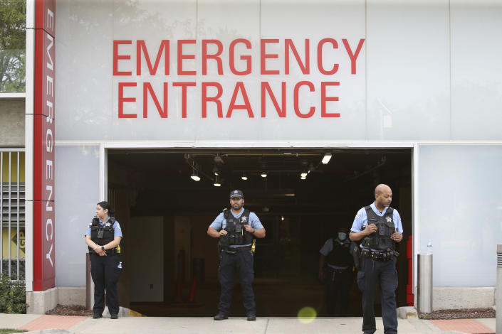 Police officers stand outside Advocate Christ Medical Center after multiple law enforcement officers were shot in the Morgan Park area of Chicago on Wednesday, July 7, 2021. Police say three undercover law enforcement officers were shot and wounded while driving onto an expressway on Chicago's South Side. (Antonio Perez/Chicago Tribune via AP)