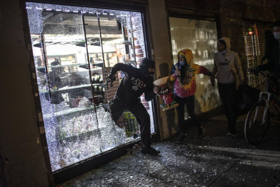 People run out of a smoke shop with smoking instruments after breaking in as police arrive on Monday, June 1, 2020, in New York. Protests were held throughout the city over the death of George Floyd, a black man in police custody in Minneapolis who died after being restrained by police officers on Memorial Day. (AP Photo/Wong Maye-E)