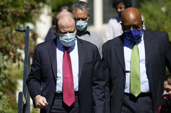 Colorado Gov. Jared Polis, left, confers with Rico Munn, superintendent of Aurora, Colo., Public Schools, as they head into a news conference about the increase in COVID-19 cases in the state and how parents need to enroll their children in school during the pandemic Tuesday, Sept. 29, 2020, in Denver. (AP Photo/David Zalubowski)