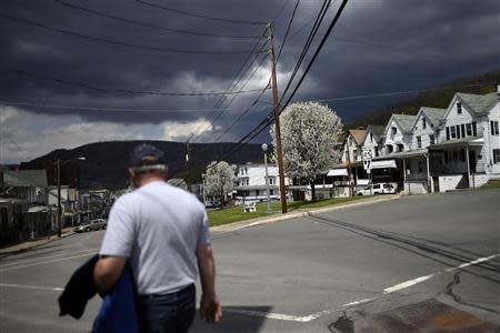 A man walks down Market Street with darkening clouds forming above the bluff in the distance in Shamokin
