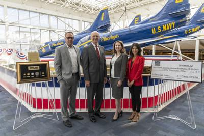 """On Veterans Day, U.S. Money Reserve presented the Naval Aviation Museum Foundation with a donation check for $60,000 and the exclusive """"Great War Series"""" set of gold and silver coins commemorating the end of WW1. Pictured from left to right: Jim Warren (VP of Marketing and Communication, USMR), retired Marine Lt. Gen. Duane Thiessen (President, NAMF), Cindy McCalip Vice President, NAMF), and Christol Farris (VP of Media, USMR)."""