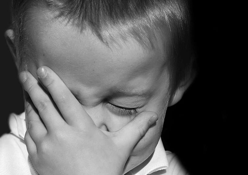 Small boy holding his face with palm