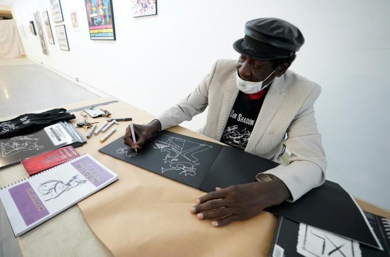 The artist known as Sir Shadow, who draws and exhibits his work in empty real estate spaces, draws one of his signature one-stroke drawings on November 25, 2020 in New York
