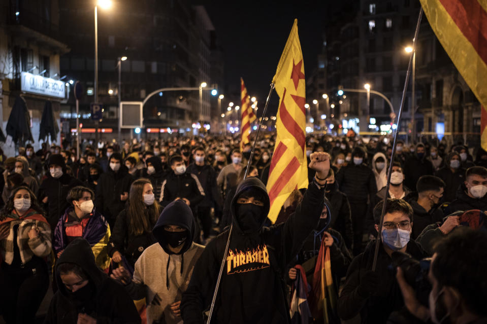People march during a protest condemning the arrest of rap artist Pablo Hasél in Barcelona, Spain, Friday, Feb. 19, 2021. The imprisonment of a rap artist for his music praising terrorist violence and insulting the Spanish monarchy has set off a powder keg of pent-up rage this week in Spain. The arrest of Pablo Hasél has brought thousands to the streets for different reasons. The majority march under the banner of freedom of speech, but Hasél's lyrics also tap into a debate about the role of Spain's parliamentary monarchy after financial scandals involving the royal house. (AP Photo/Felipe Dana)
